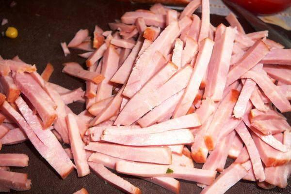 Нарежьте ветчину соломкой. Теперь все компоненты выложите на плоскую тарелку горками, рядом друг с другом. А в центр нашего цветка положите сухарики. Подавайте вместе с майонезом или сметаной в отдельной посуде.