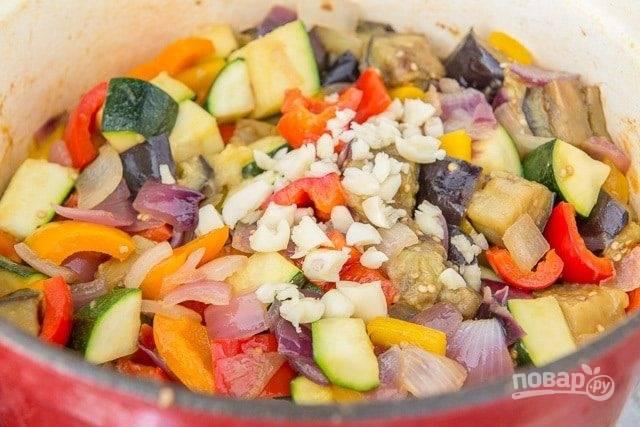5. Далее поставьте средний огонь. Добавьте масло и смешайте все овощи. Сверху насыпьте измельчённый чеснок.