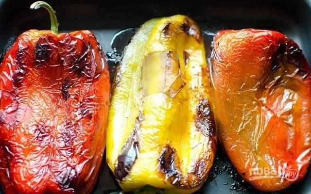 1.Вымойте, высушите болгарские перцы, выложите на противень и запекайте в духовке, разогретой до 240°, в течение 20-25 минут, переворачивая, чтобы овощи запеклись со всех сторон.