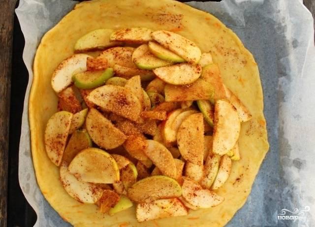Сверху на тесто уложите фруктовую начинку. Присыпьте её сахаром. К середине сложите концы теста.