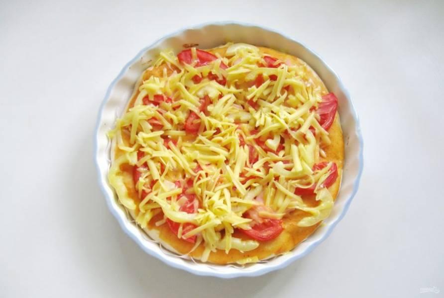 Посыпьте пиццу тертым сыром. И отправьте опять в духовку.