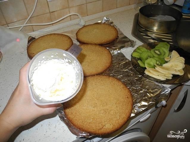 Готовый бисквит разрежьте вдоль на несколько коржей. Сделайте крем. Для этого взбейте сливки и сахар при помощи миксера. Выложите крем между коржами. Порежьте бананы и киви и выложите их на крем. Оставьте торт охлаждаться на час-два.