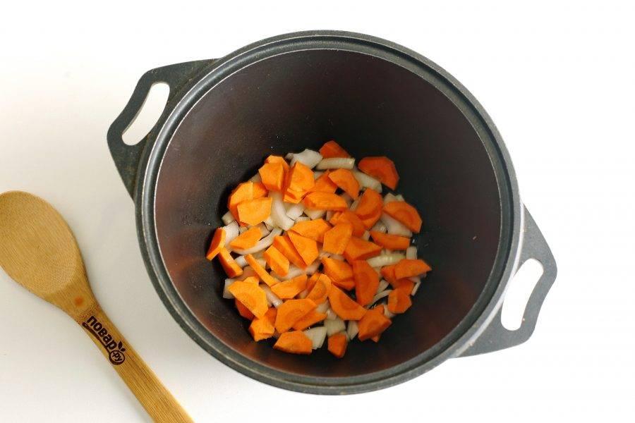 В казан налейте масло. Накалите его и выложите нарезанные произвольно лук и морковь.