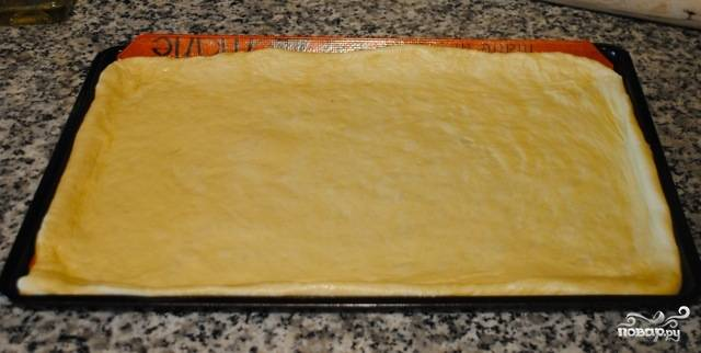 Раскатанное тесто переносим в слегка смазанный маслом противень, разравниваем, формируем бортики.