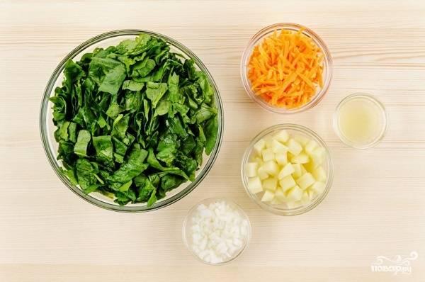 1. Первый этап — подготовка ингредиентов. Вымойте и очистите луковицу и картофель, нарежьте мелкими кубиками. Морковь натрите на средней терке. Выжмите немного сока лимона. Шпинат вымойте, обсушите и нарежьте помельче.