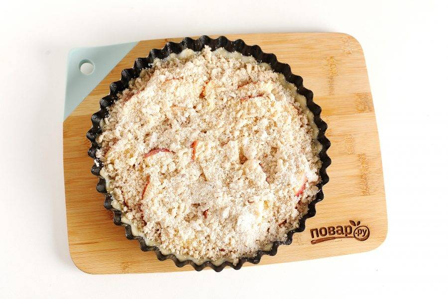 Смешайте все ингредиенты для посыпки и превратите их руками в крошку. Высыпьте ее поверх яблок. Затем разогрейте духовку до 180 градусов и запекайте в течение 40 минут.