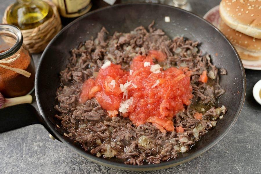 Когда фарш хорошо протушится, слейте лишний жир, добавьте натертый помидор и измельченный чеснок, продолжайте тушить еще минуты 3.