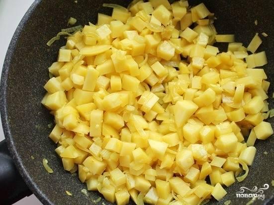 Кусочки картофеля, промытые под водой, тщательно высушите. Для этого выложите их на расстеленное полотенце. Затем бросьте картошку в сковородку к остальным овощам. Обжаривайте три минуты.