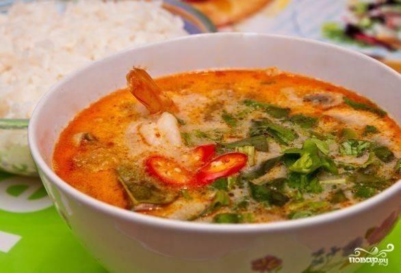 5. Варим суп еще минутку, а после выключаем. Моем и нарезаем зелень и перец чили, добавляем их непосредственно в тарелку. Если в тарелку попадают листья лайма, лемонграсс и галангал, их обязательно вынимаем, ни в коем случае не едим. Отдельно отвариваем рис. Традиционно подаем его к горячему супу.