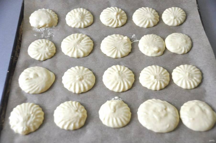 Выложите ложкой печенье на бумагу для выпечки или переложите тесто в кондитерский мешок и отсадите его.
