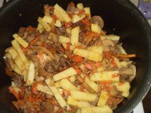 Затем картофель и маринованные шампиньоны добавляем в сковородку, перемешиваем и тушим на небольшом огне практически до полной готовности картофеля.