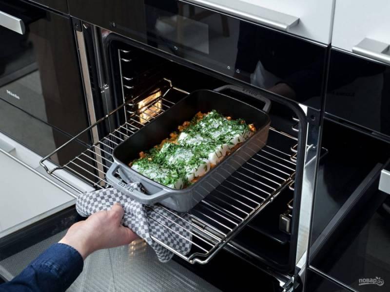 3. После этого в картофель выложите треску. Посыпьте её солью и мелко нарубленной петрушкой.