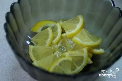 Лимончик вымойте и нарежьте тонкими ломтиками. Если будут встречаться косточки, обязательно их удалите. Счищать кожуру не надо, цедра придаст блюду особую пикантность и аромат.
