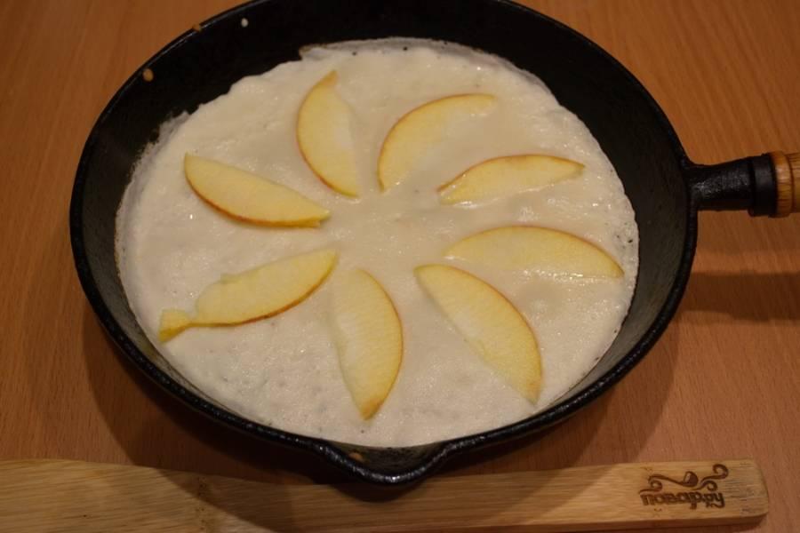 Из полученного теста жарим блинчики. Вливаем порцию для одного блинчики. Нарезаем быстро яблоки и выкладываем сверху в один ряд на еще сырое тесто. Жарим на небольшом огне. Поддеваем лопаткой блин, переворачиваем.
