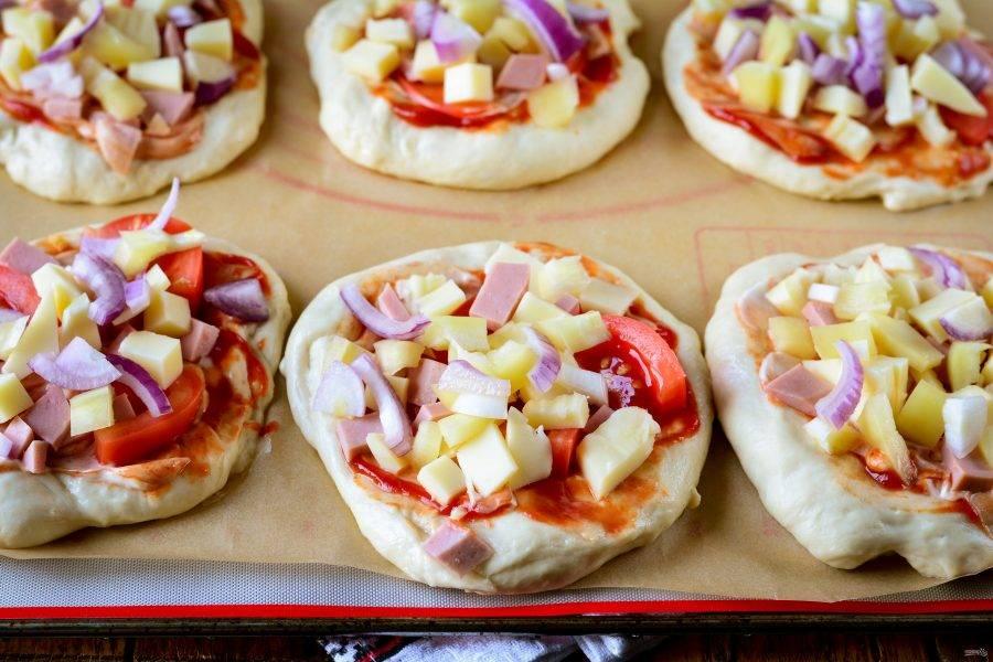 Сверху на пиццу выложите кусочки колбасы, лука, сыра и помидоров.