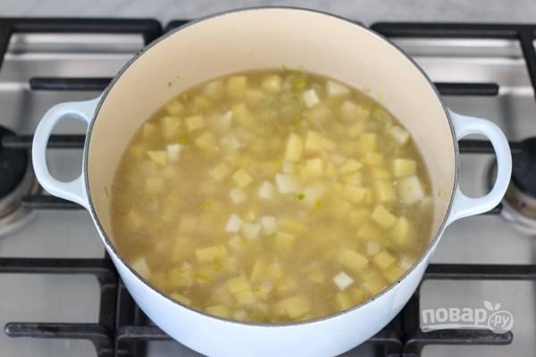 7. Доведите до кипения, выложите в кастрюлю нарезанный кубиками картофель. Посолите и поперчите по вкусу. Варите на среднем огне минут 15.