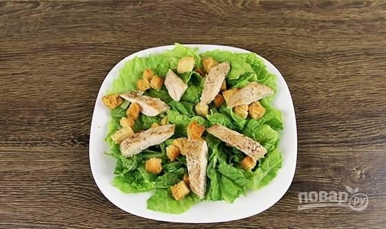 Затем на салат выложите курицу крупными кусочками. Разложите крутоны.