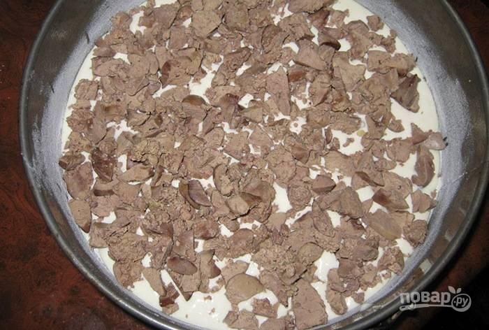 На дно формы для выпечки влейте немного масла и посыпьте муку. Влейте половину теста. Выложите печень кусочками. Посолите её и поперчите.