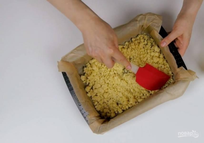 3. Перемешайте до однородности, добавьте желток и еще раз перемешайте. Переложите смесь в миску, размешайте, чтобы не было крупных комков, накройте пленкой и отправьте в холодильник на 30 минут. Половину теста слегка утрамбуйте по дну формы, застеленной бумагой для выпечки.