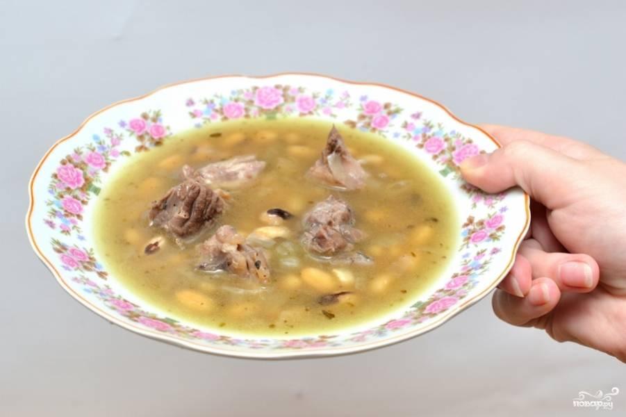Кусочки мяса выложите в суп. Подавайте суп с окороком украсив зеленью.