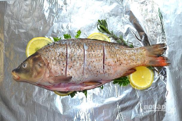 Рыбу посолите и поперчите со всех сторон. Сделайте на спинке несколько надрезов.