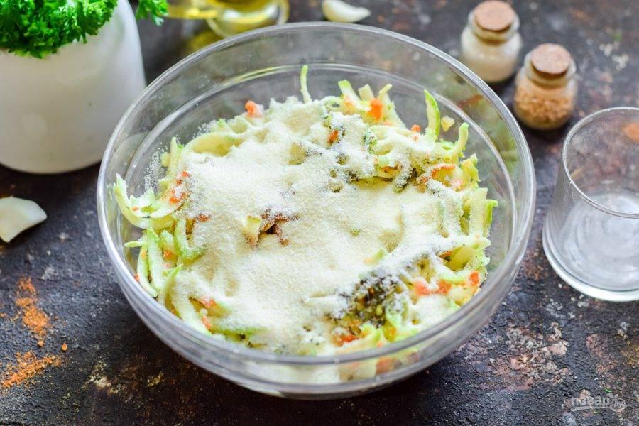 Всыпьте следом манную крупу в миску с овощами.