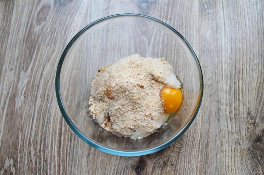 Всыпьте в миску с фаршем и яйцами панировочные сухари.