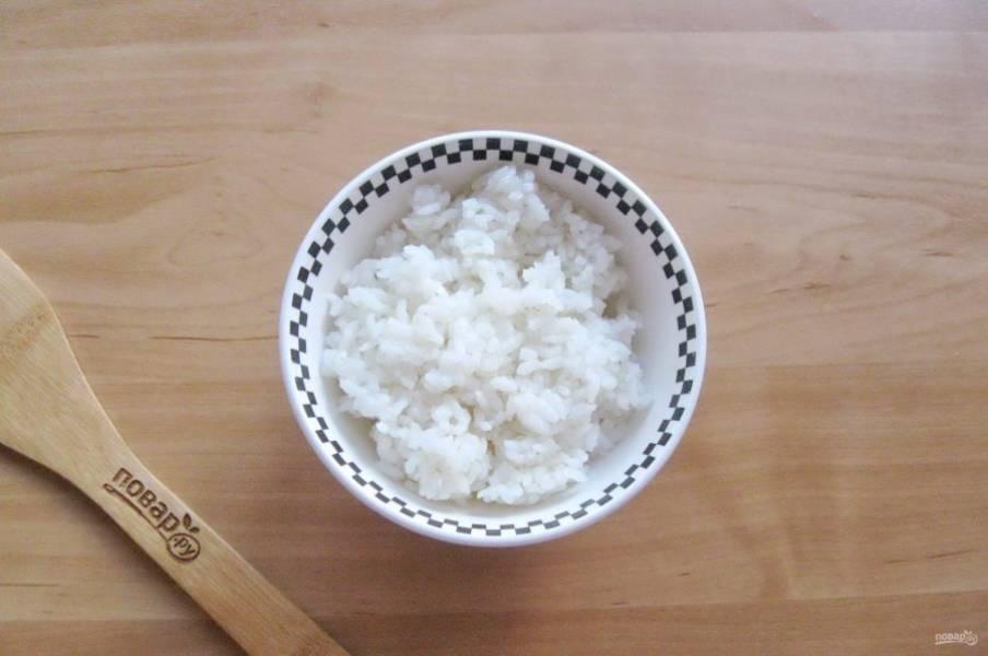 Рис отварите. Для этого в кастрюлю с водой выложите промытый рис, немного посолите и варите до готовности. После воду слейте и промойте рис снова чистой, кипяченой водой.