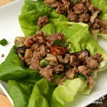 3. Смешать все ингредиенты для соуса в маленькой миске. Выложить листья салата на большое блюдо. Сверху выложить мясную смесь. Полить соусом непосредственно перед подачей на стол.