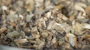 Добавляем порезанные шампиньоны и жарим до полного испарения жидкости с грибов.