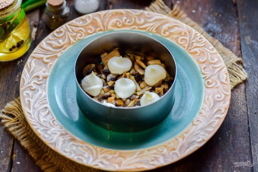 Возьмите тарелку для салата, в центре установите формовочное кольцо. Выложите грибы первым слоем, смажьте майонезом.