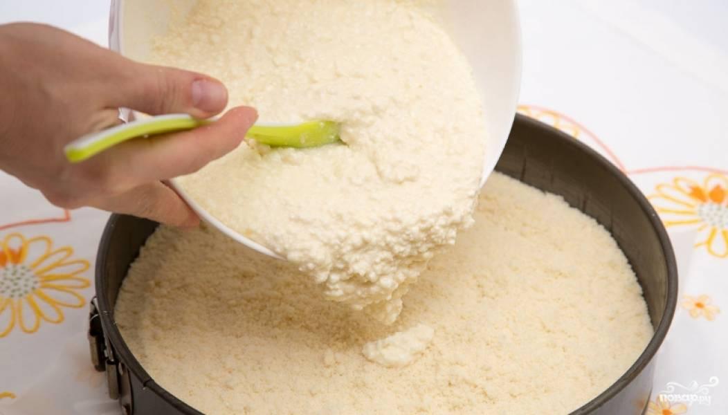 2. Отдельно смешаем творог с оставшимся сахаром, добавим яйца и ванильный сахар, смешаем и получим однородную массу. Ее выкладываем поверх первого слоя крошки.