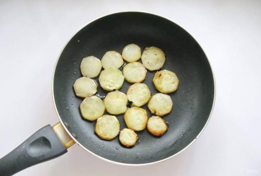 Обжарьте кружки баклажана до легкой румяной корочки с обеих сторон.