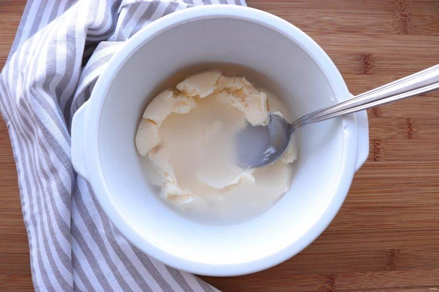 Далее масло нужно промыть. Для этого переложите его в глубокую миску и залейте холодной кипяченой водой. При помощи ложки разминайте масло. Воду слейте и повторите процедуру еще два раза.