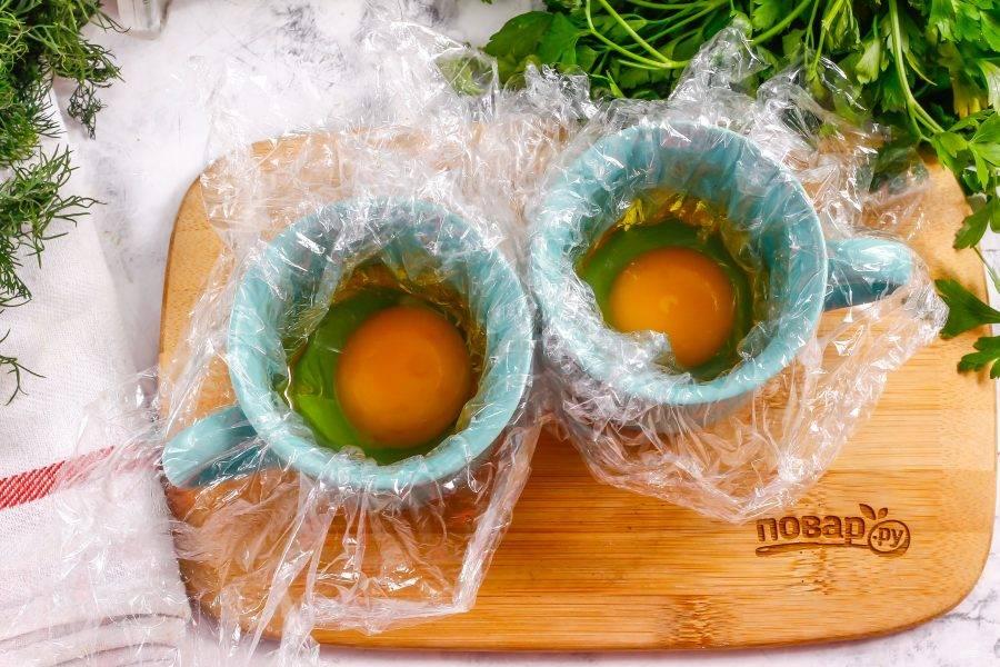 В чашки выложите пищевую пленку и смажьте ее внутри растительным маслом. Вбейте внутрь каждой чашки по 1 куриному яйцу.