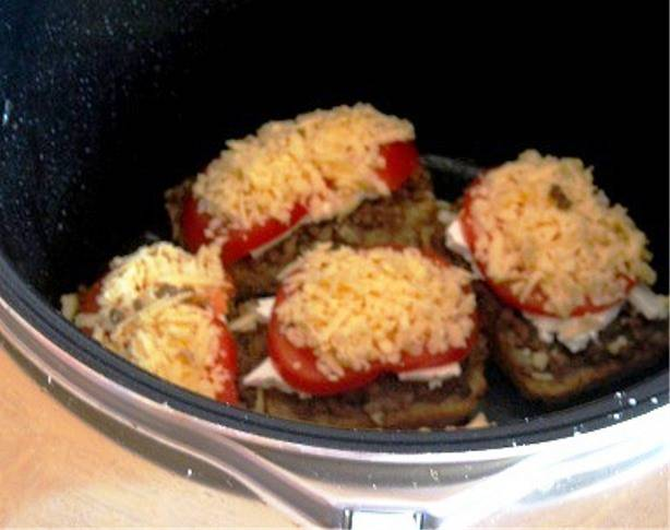 Затем посыпьте тертым сыром и запекайте в мультиварке в режиме «Выпечка» в течение 25 минут. Готовый бутерброд посыпьте измельченным зеленым луком и подавайте на стол.