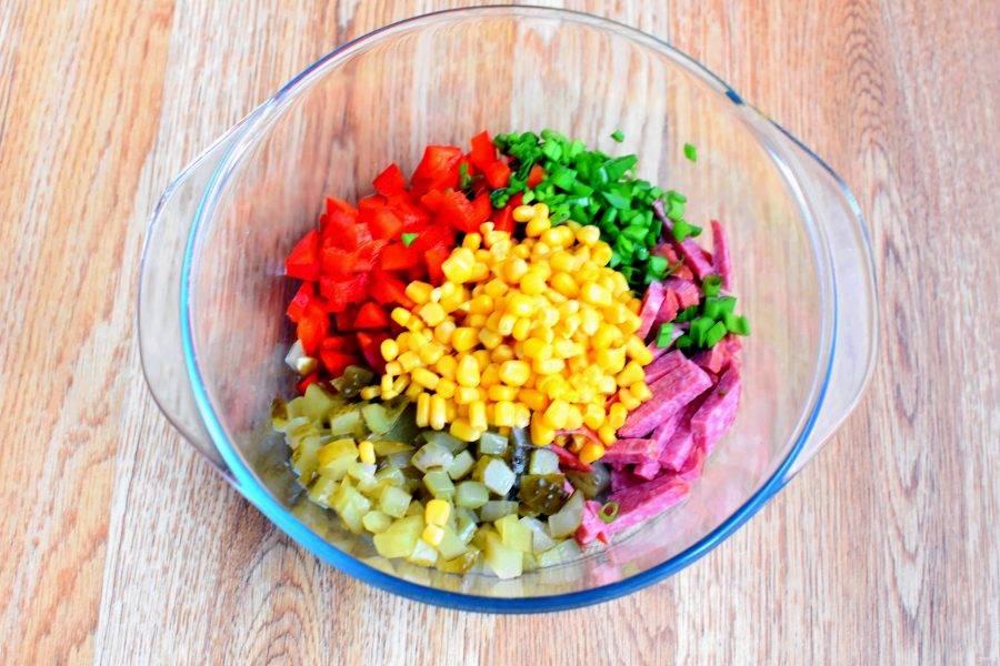 Нарежьте колбасу нетолстыми брусочками. Огурцы и перец нарежьте кубиками. Измельчите лук и обсушите консервированную кукурузу. Смешайте все в просторной миске.