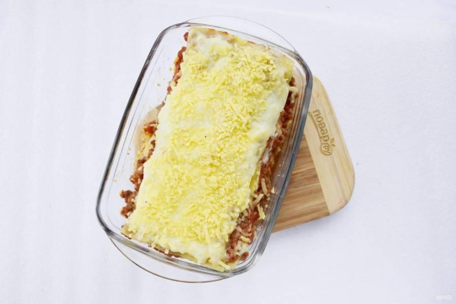 Верх лазаньи посыпьте тертым пармезаном. Поставьте запекаться в разогретую духовку на 20-25 минут.