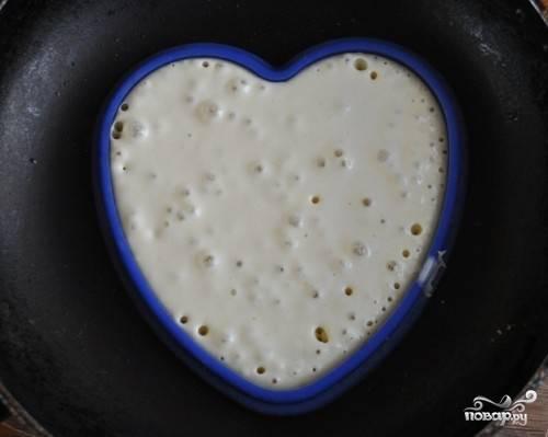 3. Формочку в виде сердечка положите в центр сковороды. Прогрейте сковородку. В формочку аккуратно влейте порцию теста. Как только начнут лопаться пузырьки в тесте, аккуратно поднимите формочку и переверните блинчик. Поддерживайте огонь чуть меньше среднего.