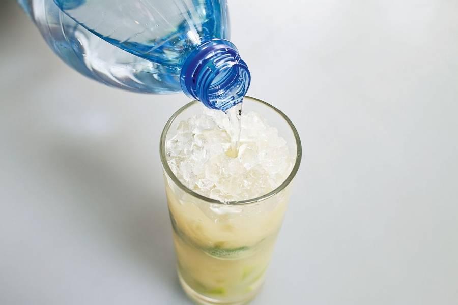 Если хотите лимонад послаще, можно добавить сахарный сироп (только совсем чуть-чуть). Не забудьте размешать его при помощи ложки с длинной ручкой. Влейте газированную воду.