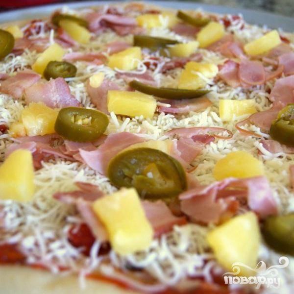 Разлить 1 чашку соуса по коржу, добавить сыр. Выложить на основу ветчину, бекон, кусочки ананаса и перца халапеньо.