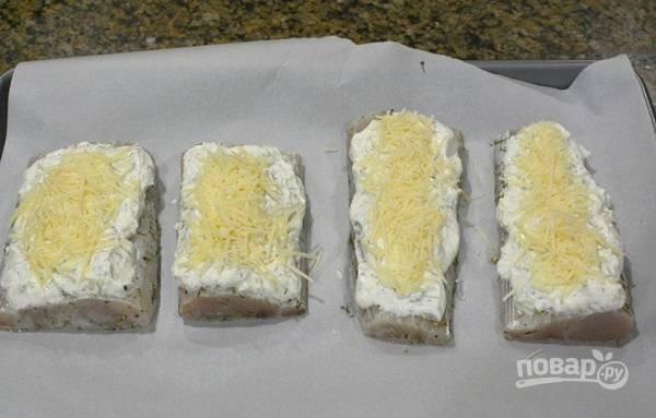 5. Вымойте и обсушите филе трески. Выложите на противень, застеленный пергаментом. Сверху распределите соус. Присыпьте тертым сыром.