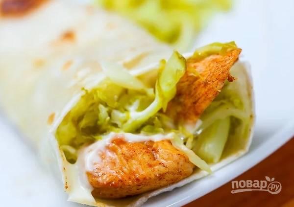 5. Каждый лаваш разрежьте пополам. Смажьте соусом, выложите курицу и капусту. Аккуратно заверните. При желании поджарьте немного на сухой сковороде. Приятного аппетита!