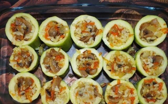 Выставляем кабачковые стаканчики в форму для запекания, смазанную растительным маслом. Заполняем стаканчики рисово-грибным фаршем.