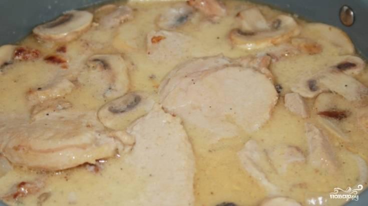 5.Переложите к свинине лук, влейте сливки и грибной бульон. Посолите и поперчите блюдо. Поставьте на огонь.
