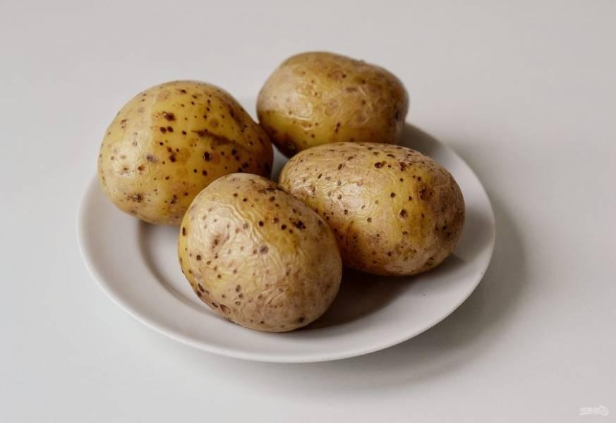 Картофель отварите в мундирах. Остудите, затем нарежьте кубиками.