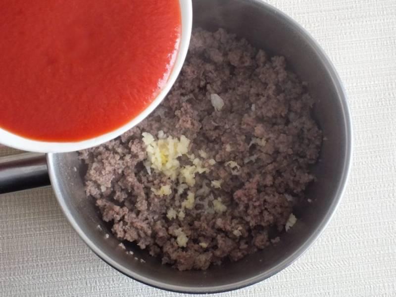 Далее добавьте измельченный чеснок, томатный соус, убавьте огонь, закройте крышкой и уваривайте до исчезновения жидкости.