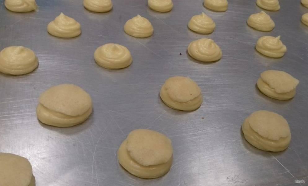 На противень для выпечки отсадите небольшие порции заварного теста.  Учитывайте, что при выпекании они увеличатся в размерах.  Сверху на них выложите лепешечки из теста кракелин.  Поставьте в духовку при 190 градусах на 15-20 минут. Готовьте до золотистой румяности.