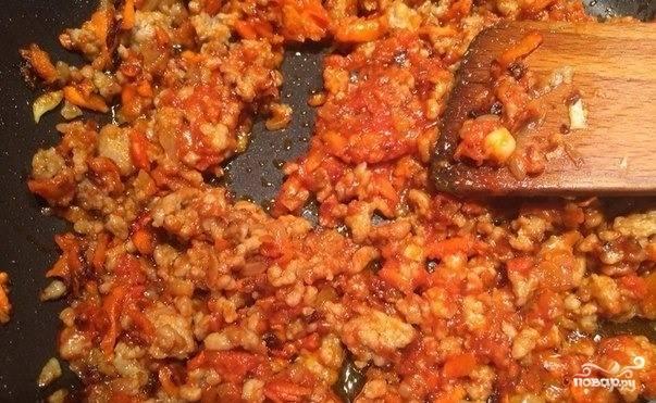 На второй сковороде пассеруйте морковь и лук на рафинированном подсолнечном масличке. Для этого натрите морковку на терке, а лук нарежьте как можно мельче. Когда овощи приобретут желтый оттенок, добавьте к ним томатную пасту и фарш. Перемешайте и обжаривайте около пяти минут.