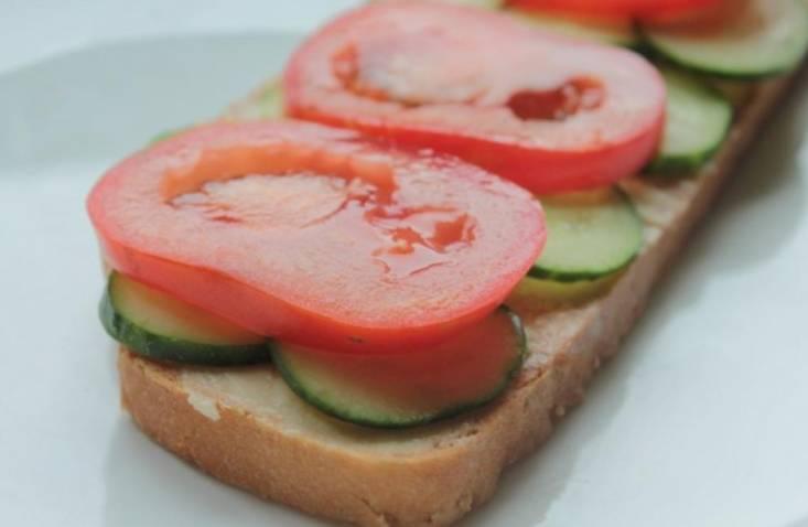 Смажьте ломтики хлеба маслом. Сверху выложите кружочки помидоров, огурцов и порезанного вареного яйца.